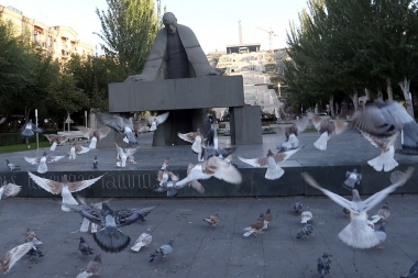The flock of pigeons fly over Al. Tamanyan statue of Yerevan, Armenia - Photolure News Agency